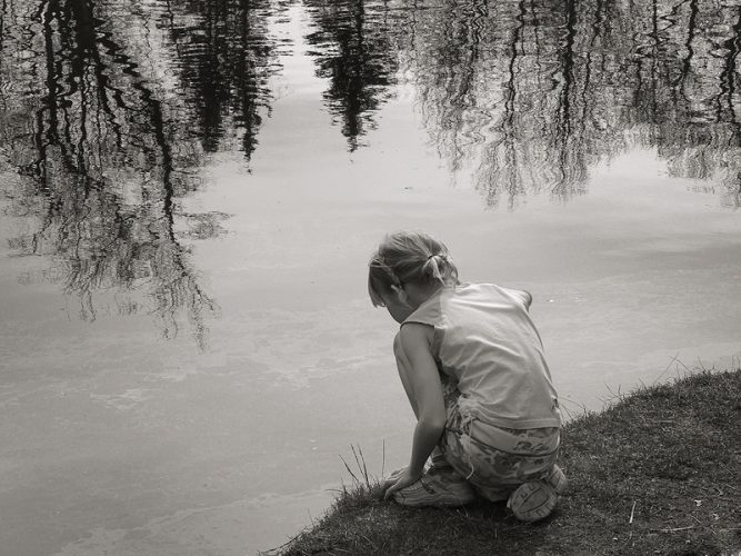 Girl at waters edge in park